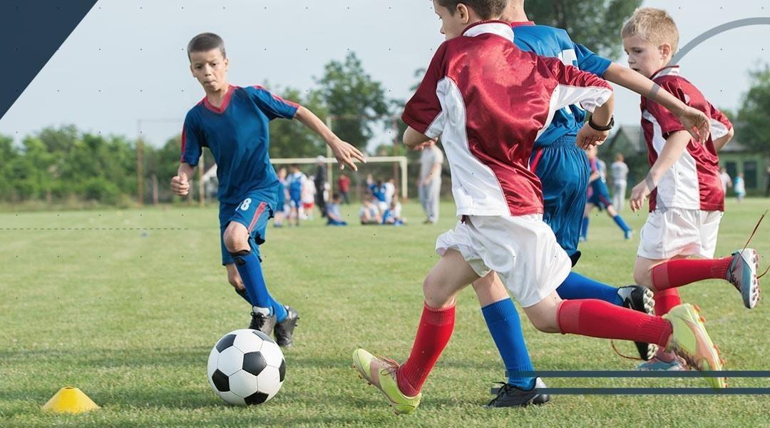 Il piede e la caviglia del bambino che gioca a calcio