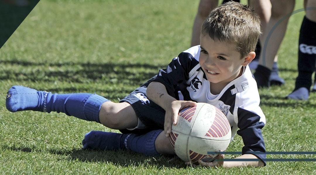 Il piede e la caviglia del bambino che gioca a rugby
